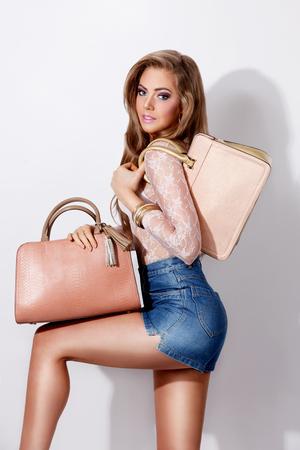 minifalda: Mujer atractiva que presenta con los bolsos de la moda