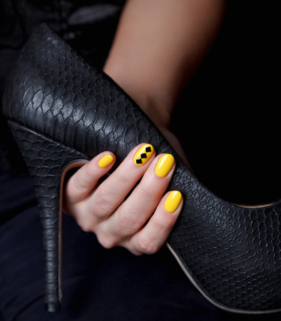 uñas pintadas: mujer que sostiene una hermosa estilete atractivo con uñas amarillas