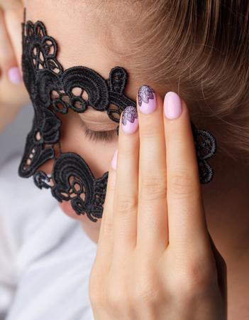 Vrouw die een kanten masker met kanten romantische mooie nagels
