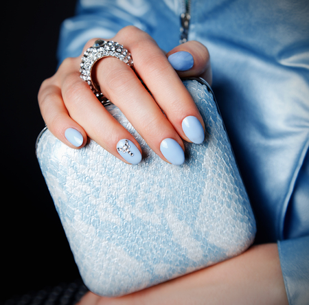 baby blue: Close-up of pretty party clutch bag with matching blue nails