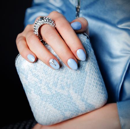 Close-up van mooie party clutch bag met bijpassende blauwe spijkers