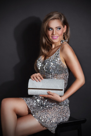 Sexy woman in a party dress with matching clutch bag