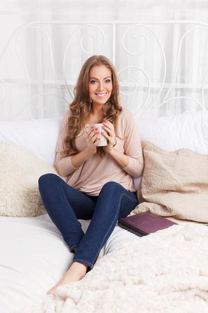 Mooie vrouw ontspannen met een kop warme drank in het bed