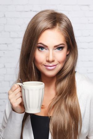 Close-up van een mooie vrouw met een kop hete drank Stockfoto