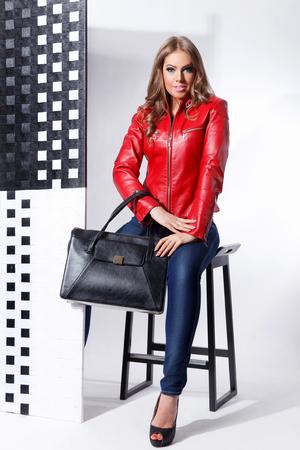 Mooie vrouw poseren in lederen jas met een zak