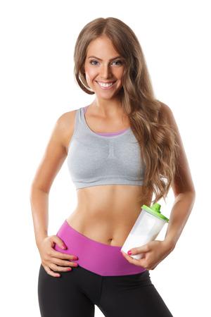 cintura: Hermosa mujer de ajuste feliz posando con una botella de batidos de proteínas