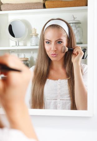 Mooie vrouw die op make-up met een borstel in de badkamer