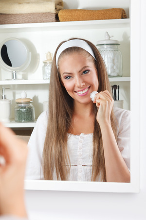cotton ball: Beautiful happy woman cleaning her face with a cotton ball in the bathroom
