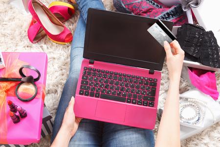 Vrouw winkelen online met een laptop en een creditcard