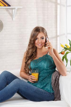 Mooie vrouw praten over de telefoon thuis Stockfoto