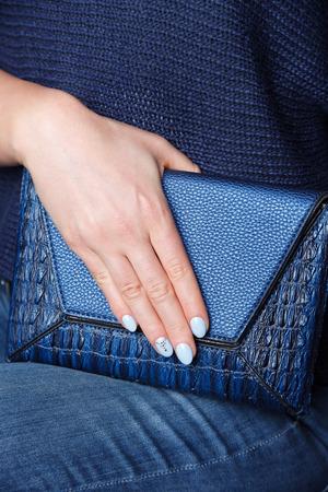 Close-up van een blauwe lederen tas met bijpassende nagels