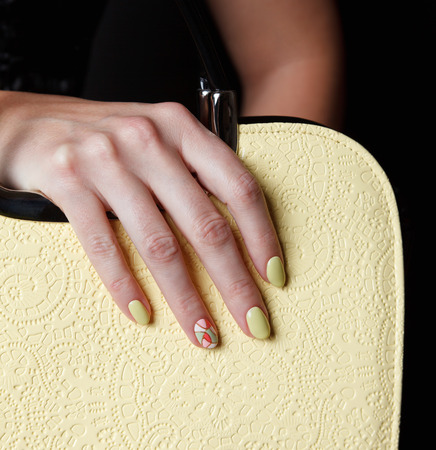 Close-up van gele nagels op trendy lederen tas