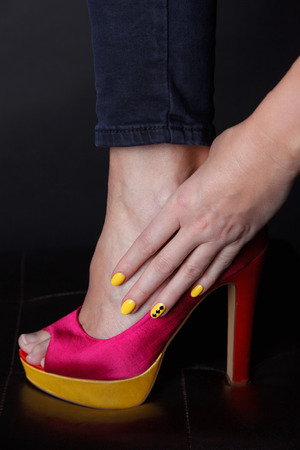Close-up van gele nagels mode met bijpassende hoge hakken Stockfoto