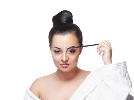 Beauty woman fixing her makeup Eyebrows with a brush isolated on white Stock Photo