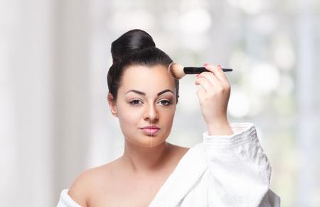 Beautiful woman fixing her makeup with face powder