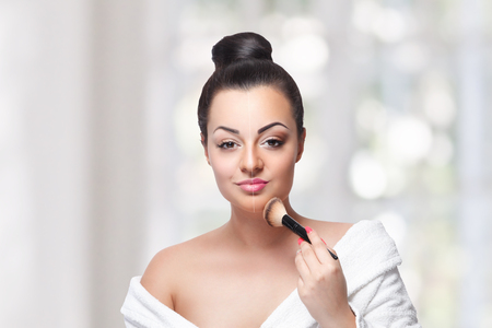 Beautiful woman putting on foundation makeup with brush