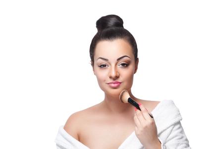 Mooie vrouw contouren haar kin met een make-up kwast Stockfoto