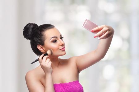 Mooie vrouw die een Selfie maakt terwijl ze haar make-up maakt