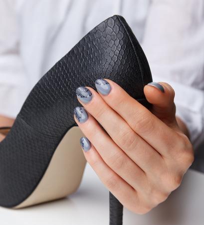 uñas pintadas: La mujer con las uñas hermosas pintadas que sostiene un zapatos de tacón alto