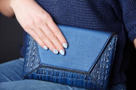 Close-up van een lederen envelop tas met bijpassende blauwe spijkers