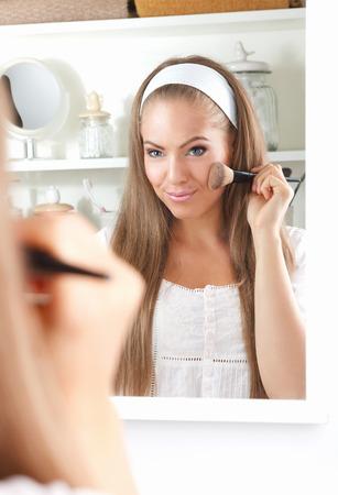 Mooi meisje dat Broner op haar wang met een make-up kwast Stockfoto - 66375516
