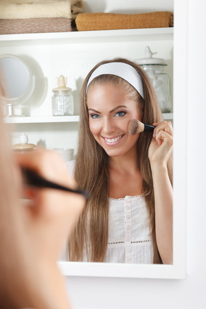 Mooie jonge vrouw die blos op haar wang Stockfoto