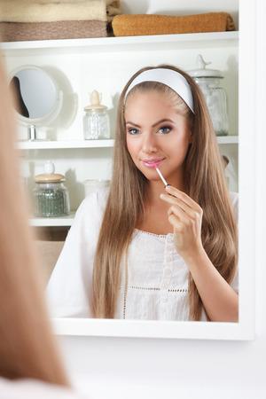 Mooie vrouw die lipgloss op haar lippen in de badkamer Stockfoto - 66337769