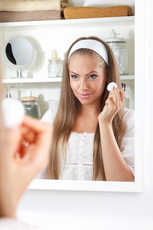 Mooie vrouw het schoonmaken van haar gezicht met een katoenen bal in de badkamer Stockfoto