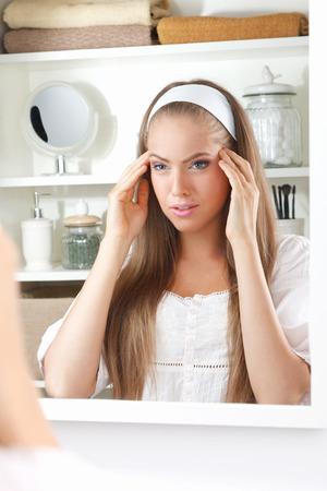 Beautiful woman massaging her temporal Standard-Bild