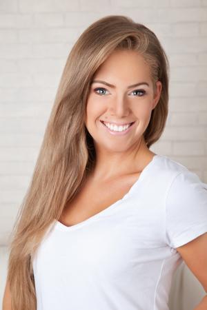 Close-up portret van een lachende mooie jonge vrouw met lang haar natuurlijke