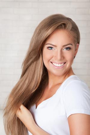 Mooie gelukkige vrouw aan te raken haar lange haar natuurlijke Stockfoto