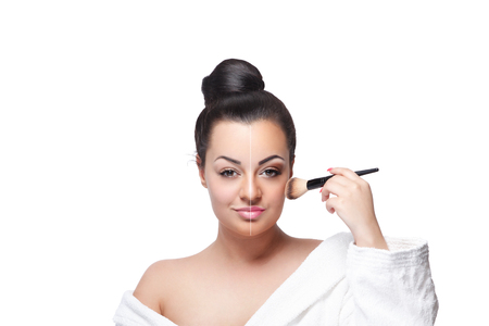 Beautiful young woman applying blush with a makeup brush Imagens