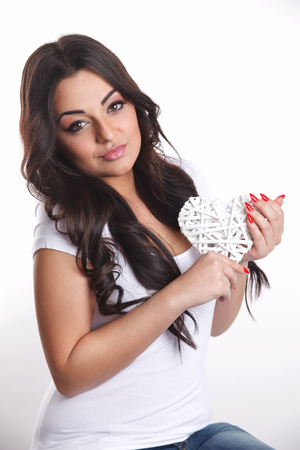 Beautiful young woman holding a heart shaped decoration Imagens