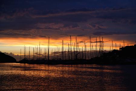 Silhouetten van zeilboten in zonsondergang