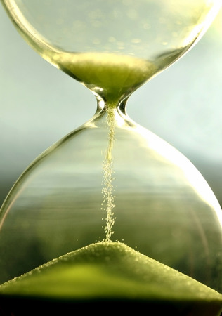 close up hourglass counting down time with moving sand  view,green Archivio Fotografico