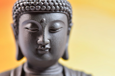 The face of Buddha Zen sculpture on a yellow background