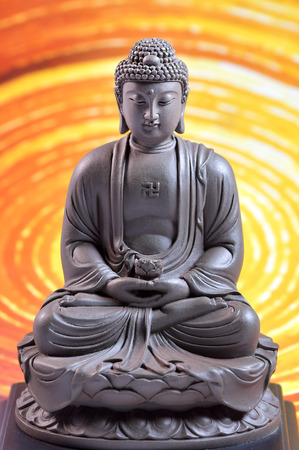 Zen Buddha sculpture on the  yellow background Stock Photo