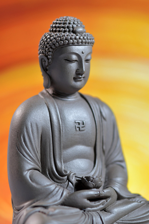 Zen Buddha sculpture on the yellow background