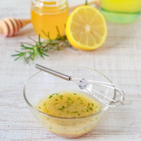 그릇에 올리브 오일, 꿀, 레몬, 겨자 샐러드 드레싱