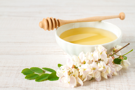 honey with acacia blossoms on a white wooden background Stock Photo