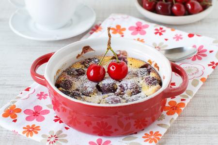 ramekin: Clafoutis with cherries in red ramekin on wooden background Stock Photo