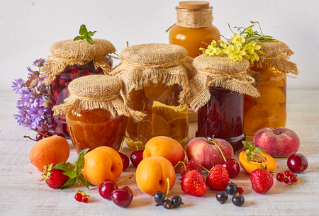 Various jams and compotes with fresh fruits on white wood Stock Photo