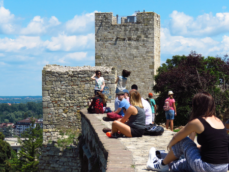 Belgrade, Serbia. July 20, 2018. Foreign tourists resting on the wall and enjoying the view from the Kalemegdan fortress.