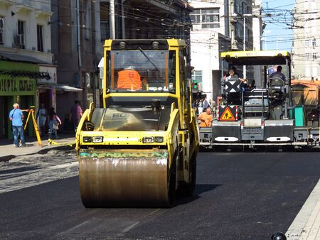 Belgrade, Serbia, October 1, 2019. Steamroller and paver finishing asphalt street in downtown. 新聞圖片