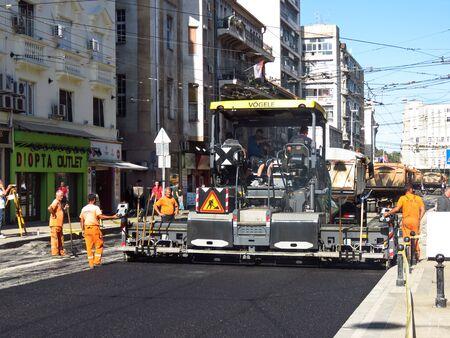 2019年10月1日、セルビアのベオグラード。アスファルト通りを仕上げる舗装機。