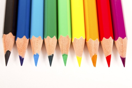 Assortment of coloring pencils arranged in a rainbow color pattern on white background photo