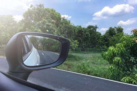 Landscape in the sideview mirror of a car , on road countryside. Reflection of sunny autumn road at the car side mirror.