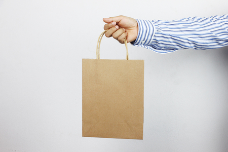 Hand of businessman holding brown paper bag and have copy space for design in your work concept.