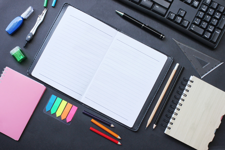 Top view notebook and pencil keyboard with accessories placed on a black desk in office and have copy space concept in your work.