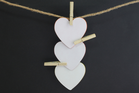 Paper heart blank on the rope with black background for your design.